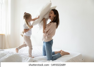 Active young mother and preschooler daughter holding pillows fighting on bed in the morning, starting day laughing having good mood positive emotions, playtime funny pastime with kid at home concept