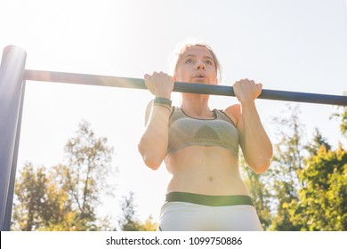 Active and young woman doing pullups.