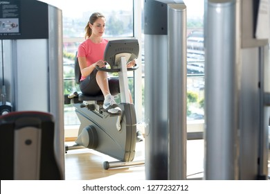 Active young woman exercising on cycling machine in gym