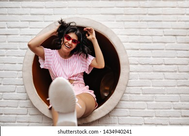 Active young woman funny posing outside. Outdoor shot of blissful girl in summer attire.