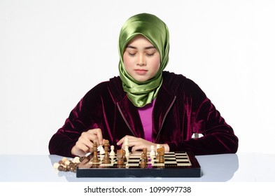 active young woman playing chess over white background