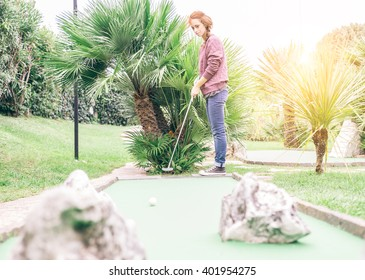 Active young woman playing minigolf in a amusement park