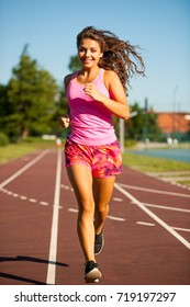 active young woman runer runs on athletic track on summer afternoon