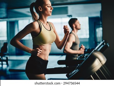 Active young woman running on treadmill with guy on background