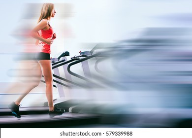 Active young woman running on treadmill at the gym exercising. Run on a machine