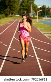 active young woman runs on atheltic track on summer afternoon