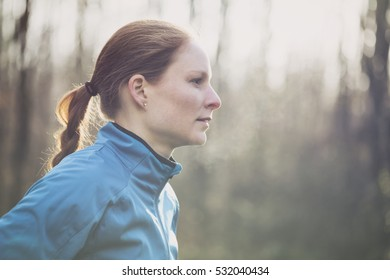 Active young woman in sportswear posing before or after a run in a park or a forest.