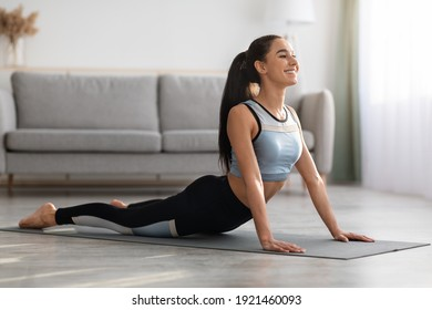 Active young woman in sportswear practicing yoga at home, laying on fitness mat in living room and stretching her body, copy space. Downward-facing dog yoga pose, yoga practice at home concept