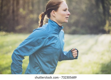 Active young woman in sportswear running in a park or a forest.
