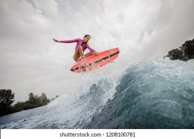 Active and young woman wakesurfer dressed in pink swimsuit jumping up the blue splashing wave against sky on a cloudy day