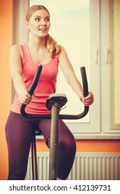 Active young woman working out on exercise bike stationary bicycle. Sporty girl training at home. Fitness and weight loss concept.