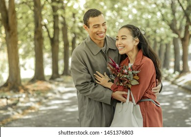 Actively laughing. Joyful short-haired boyfriend in grey old-fashioned overcoat entertaining his beautiful girlfriend