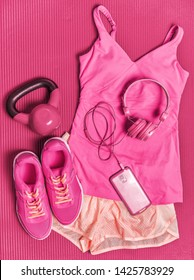 Activewear fitness clothes outfit - girly pink fashion sportswear clothing for girl training with kettlebell weights and phone headphones to listen to music during workout at gym.