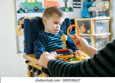 Activities for kids with disabilities. Preschool Activities for Children with Special Needs. Boy with with Cerebral Palsy in special chair play with mom at home. - Shutterstock ID 1899530617