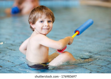 Activities on the pool, toddler boy swimming, having fun and playing in water, indoor