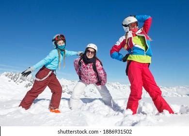 Activités sous la neige de trois jeunes filles en vacances d'hiver dans les Alpes françaises dans la neige avec veste colorée et casque de ski