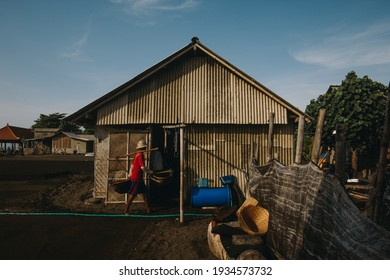 Activities of traditional salt farmers who collect seawater in small huts to make salt from seawater. huts erected on the edge of the beach, where the traditional salt production. a man who is bringin