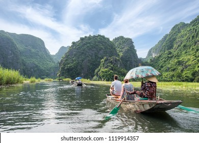 Activity downstream in mountain valley on boat with vietnamese using foot paddle in Ngo Dong river, Ninh Binh, Halong Bay on land