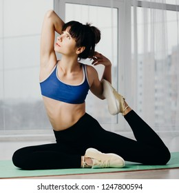 Activity, flexibility, healthy lifestyle, good mood and wellness. Young woman doing static stretching exercise to warm up before workout