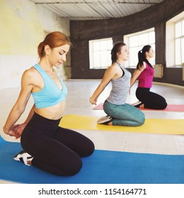 Activity, good mood, healthy lifestyle, flexibility, positivity. Group of cheerful fit women doing stretching exercises during yoga class