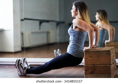 Activity, personal workout, training, self-development, vitality, sport, healthy lifestyle. Fit woman training with gym equipment, performing reverse push ups using step platform