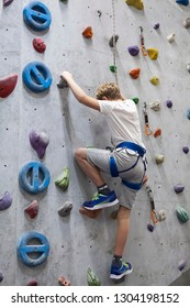 Activity of rock-climbing on artificial climbing walls, Caucasian boy with safety line
