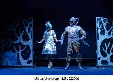 An actor dressed as a robot and an actress wearing a princess costume play a performance for children on the theater stage