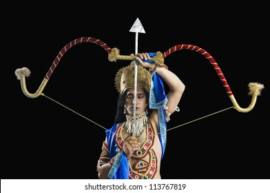 Actor dressed-up as Rama and holding a bow and arrow