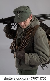 actor man in the old winter mountain uniform near the MG 42 machine gun during the Second World War posing on a gray background