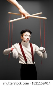Actor as a marionette controlled with ropes by a huge hand on the grey background. Concept of a human controlling