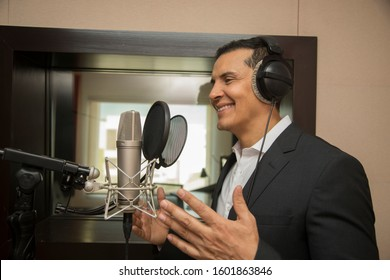 actor and radio announcer with headphones and microphone working film dubbing, performing radio spot and singing