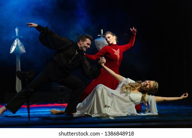Actors and actresses in red, white and black suits, on the theater stage show a dramatic performance.