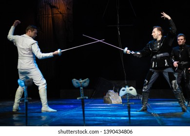 Actors in black and white clothes play a duel with swords performance on the theater stage