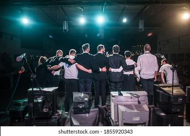Schauspieler beugen sich dem Publikum auf der Bühne nach der Aufführung vor. Lebhafter Beifall von der Menge. Theaterszene. Gehorsam gegenüber der Öffentlichkeit. Zurück-Ansicht