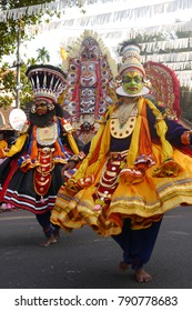 Actors with multi-colored clothes and face paintings performing traditional Kathakali dance to celebrate the New Year during a street carnival in Fort Kochi (Cochin), Kerala, India, 2016.