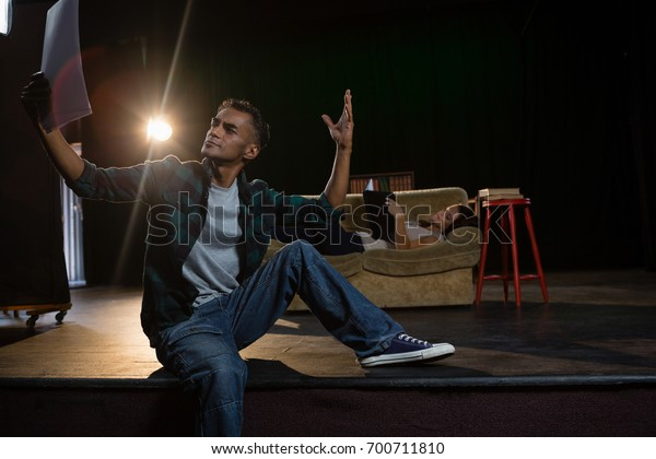 Actors reading their scripts on stage in theatre