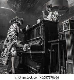 Actors in steam punk masks and antique costumes indoor. Black-white photo.
