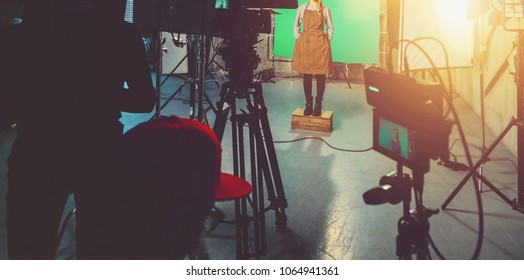 actress in apron in studio posing on green screen