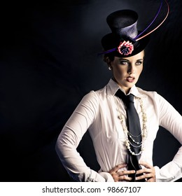 An actress dressed in typical vaudeville costume with a fascinator hat and tie performing on a darkened stage facing out of frame to an unseen audience
