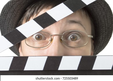 Actress with movie clapper behind face, close up image.