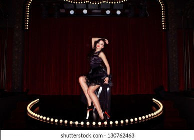Actress on the stage cabaret with red curtains and lamps