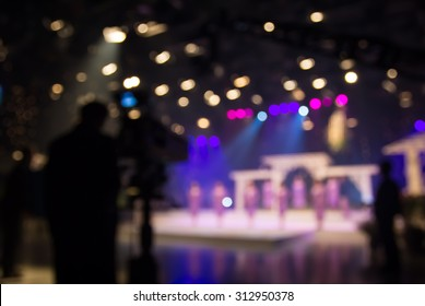 Actress or singer in studio of television station with camera and cameraman