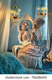 Actress sits on a chair in front of a mirror in the dressing room with perfume