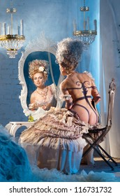 Actress sitting in the dressing room with perfume