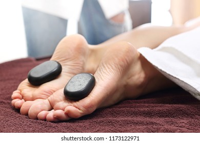 Acupressure. Massage with basalt stones.