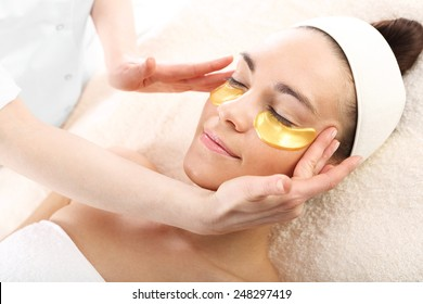 Acupressure, massage his temples, golden flakes collagen.Cosmetic procedure, the woman's face with gold flakes under the eyes and on the lips