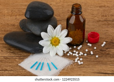 Acupuncture and Homeopathy medicine on wooden background.
