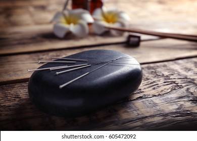Acupuncture needles with stone on wooden background
