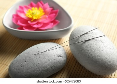 Acupuncture needles with stones on bamboo mat