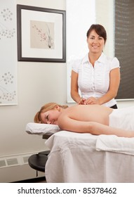 An acupuncturist placing a needle in the back of a woman patient